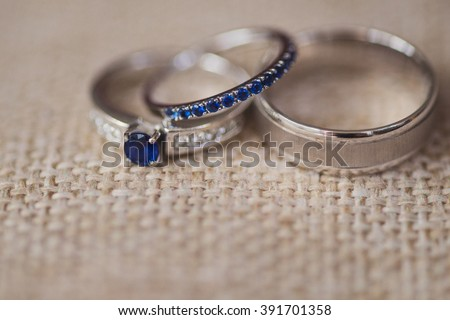 wedding rings and engagement ring with blue gemstones on natural linen background - stock photo