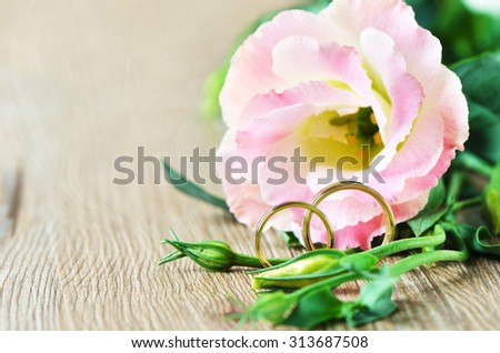 Wedding rings and Eustoma flower on wooden background/Wedding rings/Wedding rings - stock photo