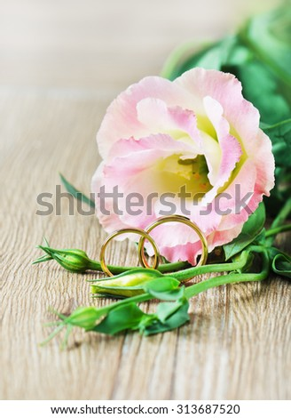 Wedding rings and Eustoma on wooden background/Wedding rings/Wedding rings - stock photo