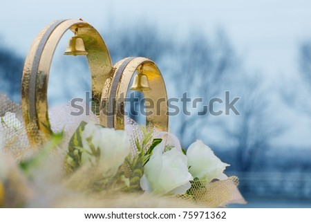 Wedding rings and flowers (decorative) on the roof of the car. Rings in the raindrops. - stock photo