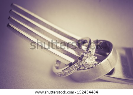 wedding rings and fork in vintage tone - stock photo