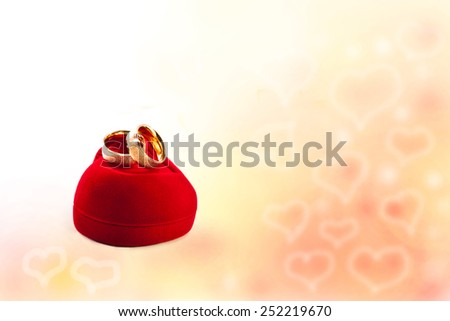 Wedding rings and gift box on a background of hearts - stock photo
