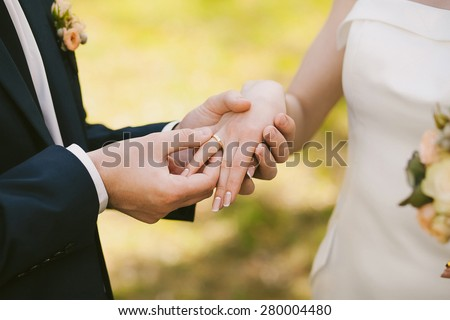 wedding rings and hands of bride and groom. young wedding couple at ceremony. matrimony. man and woman in love. two happy people celebrating becoming family - stock photo