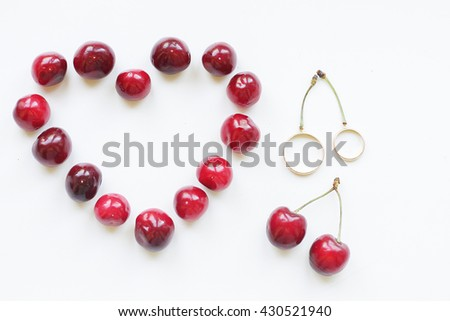 wedding rings and juicy cherries in the form of heart - stock photo