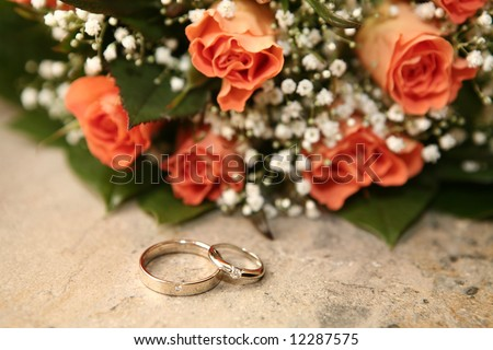 Wedding rings and orange roses - stock photo
