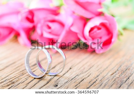 Wedding rings and pink roses on wooden background