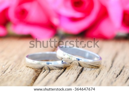 Wedding rings and pink roses on wooden background - stock photo