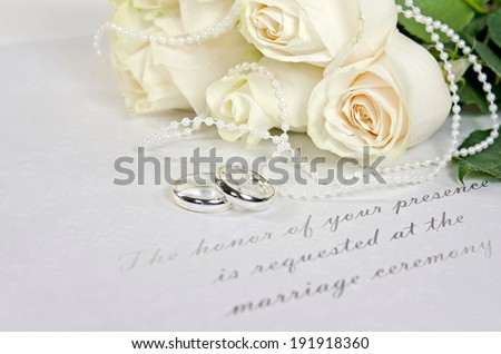 wedding rings and white rose bouquet on a formal wedding invitation - stock photo