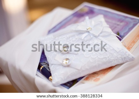 Wedding rings as wedding love symbol on the lace pillow. Beautiful wedding background. - stock photo