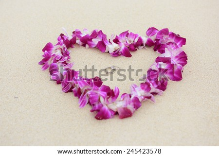 Wedding rings beach love concept. Closeup of two bands in flower heart for casual marriage celebration. - stock photo