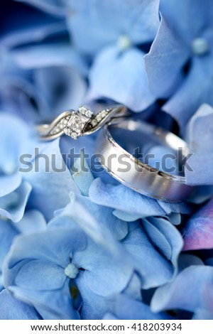 Wedding rings close up over flowers.  - stock photo