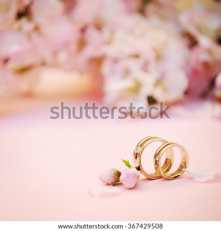 Wedding rings closeup with pink almond flowers