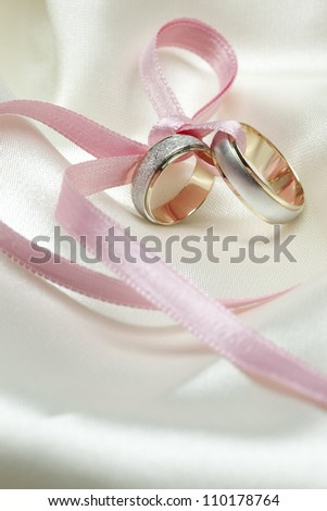 Wedding rings connected with pink ribbon - stock photo