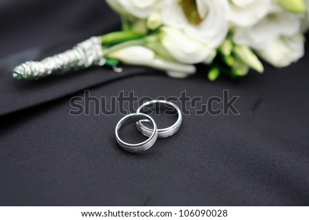 Wedding rings detail with wedding jacket and blurred groom's corsage, focused to first ring - stock photo
