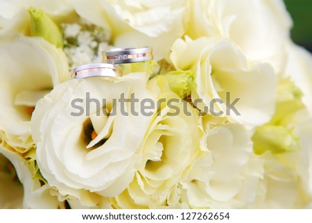 Wedding Rings detail with yellow flowers, focused to the rings - stock photo