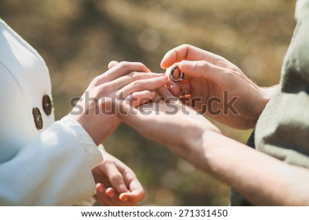 Wedding rings. Hands of bride and groom. Wedding ceremony. Wedding couple. Wedding celebration. Newlyweds. Man and woman with golden ring. Close up groom puts  wedding ring on bride - stock photo