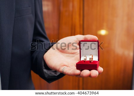wedding rings in a red box in a hand at the groom - stock photo