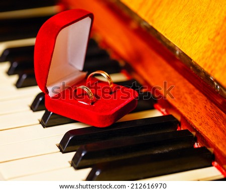 Wedding rings in a red box standing on the piano keys closeup shot