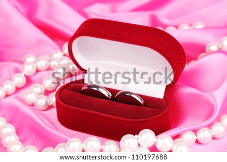Wedding rings in red box on pink cloth background