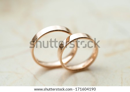 wedding rings laying on marble surface - stock photo