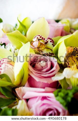 wedding rings lie on a flower in the bouquet. Rose with pearl