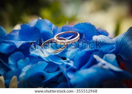 wedding rings lie on flowers - stock photo