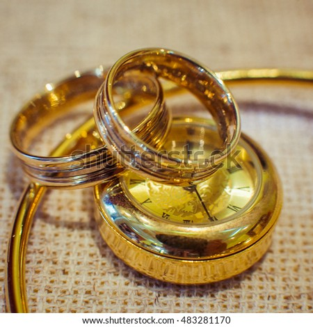Wedding rings lie on the golden watch