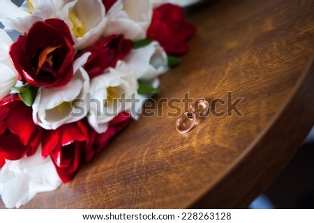 Wedding rings lying on a table with wedding bouquet of red and white tulips on background - stock photo