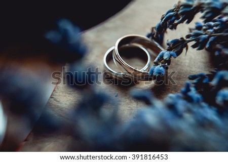 Wedding rings of gold on a table near flowers