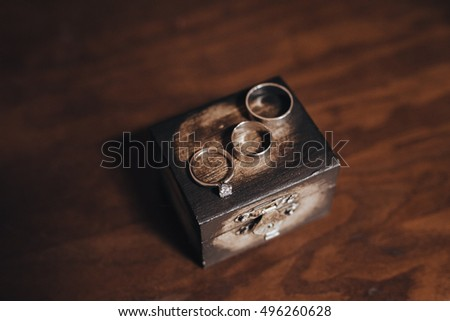 Wedding rings of the groom and bride are on the a wooden box