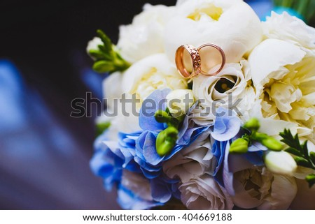 Wedding rings on a bouquet of roses - stock photo