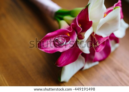 wedding rings on a bouquet on wooden background, a bouquet of Calla lilies, wedding decorations, wedding preparation, wedding rings and flowers