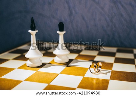 wedding rings on a chessboard. King and queen - stock photo