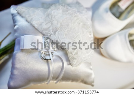 Wedding rings on a cushion, and the bride's white shoes.