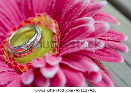 Wedding rings on a flower on a wooden table.