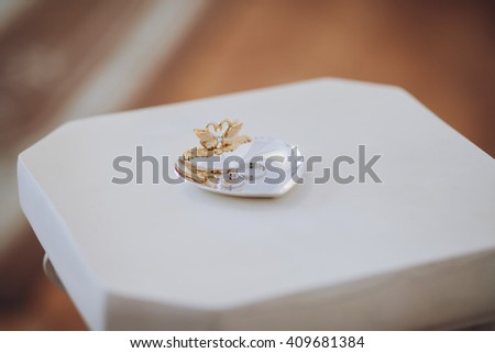 Wedding rings on a plate on a stand - stock photo
