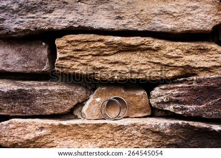 Wedding rings on a rock ledge