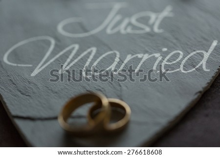 wedding rings on a slate saying just married