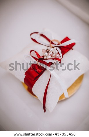 Wedding rings on a white cushion with red ribbon