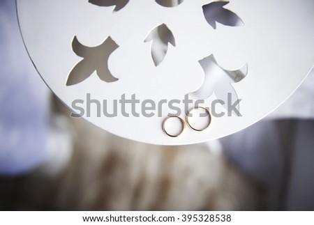 wedding rings on a white round table - stock photo
