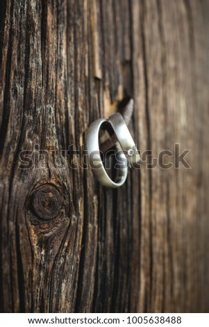 Wedding rings on an old nail fixed on a wooden plank