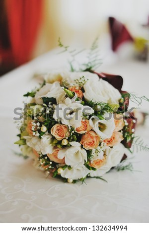 wedding rings on bridal bouquet on a table