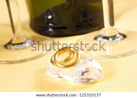 wedding rings on crystal heart on the table with champagne