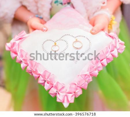 Wedding rings on cushion - stock photo