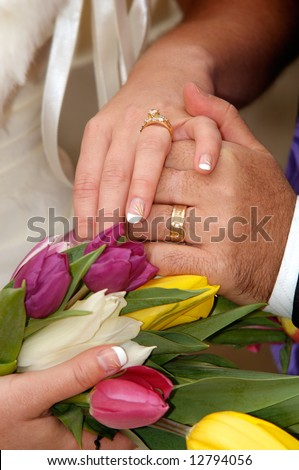Wedding rings on hand of bride and groom.