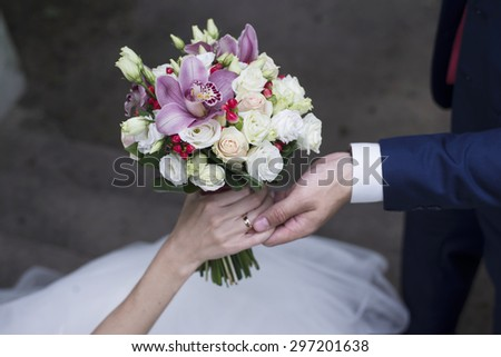 Wedding rings on hands of bride and groom. - stock photo