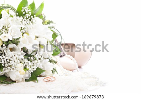 Wedding rings on lace against wedding bouquet and shoes