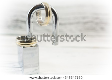 Wedding rings on opened shiny padlock on vintage white background. Concept for marriage problems - stock photo
