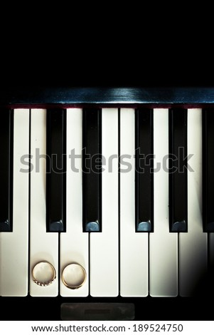 wedding rings on piano - stock photo