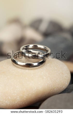 Wedding rings on rocks on bright background